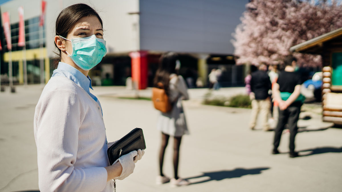 woman in facemask social distancing while waiting to enter a building