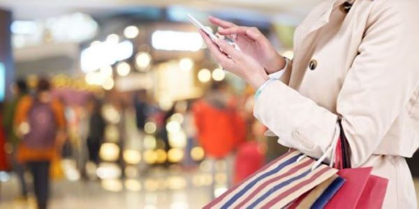 woman carrying shopping bags types on device in retail store