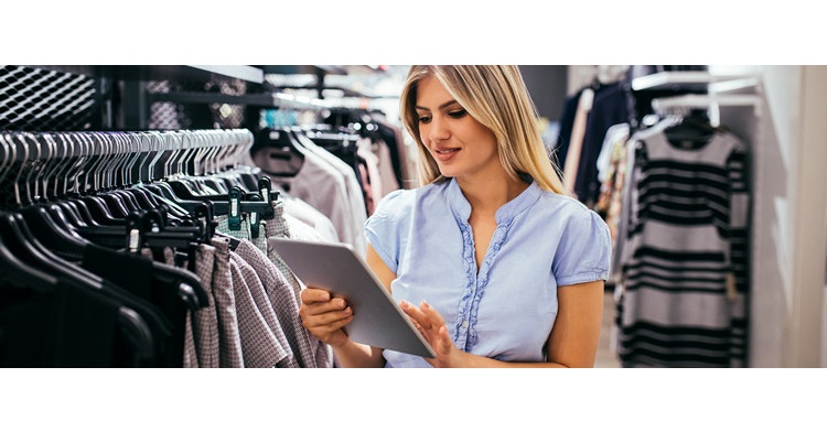 female retail associate examining tablet in front of clothing rack