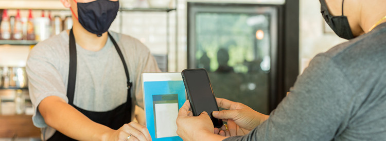 Male customer with protective mask paying bill by cell phone